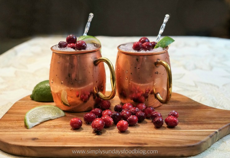 Two frozen copper cups filled with the cocktail and ice, topped with cranberries, ice wedges and stirrers. They sit on a cutting board with frozen cranberries and lime wedges