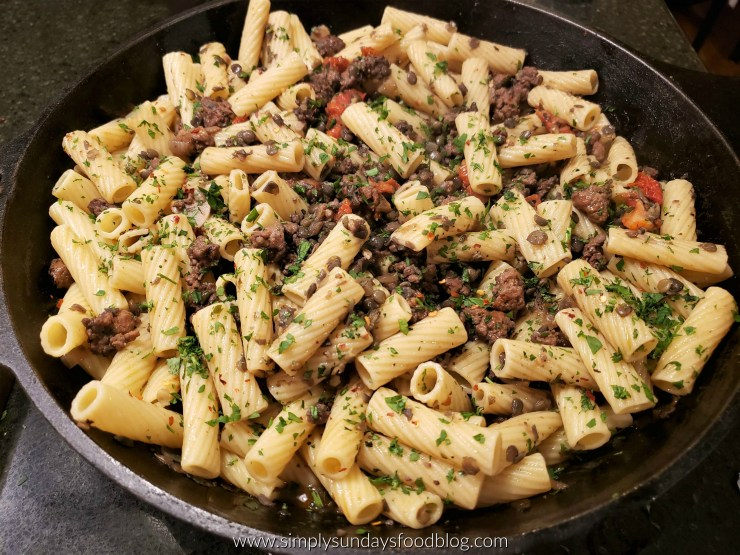 Ridged rigatoni pasta tossed with lentils, sausage, onions, red sun dried tomatoes and green fresh parsley in a black cast iron pan