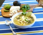 A bowl of roasted poblano posole garnished with avocado, lime and fresh cilantro on a blue striped cloth with cheese, cilantro, avocado and lime on a cutting board in the background