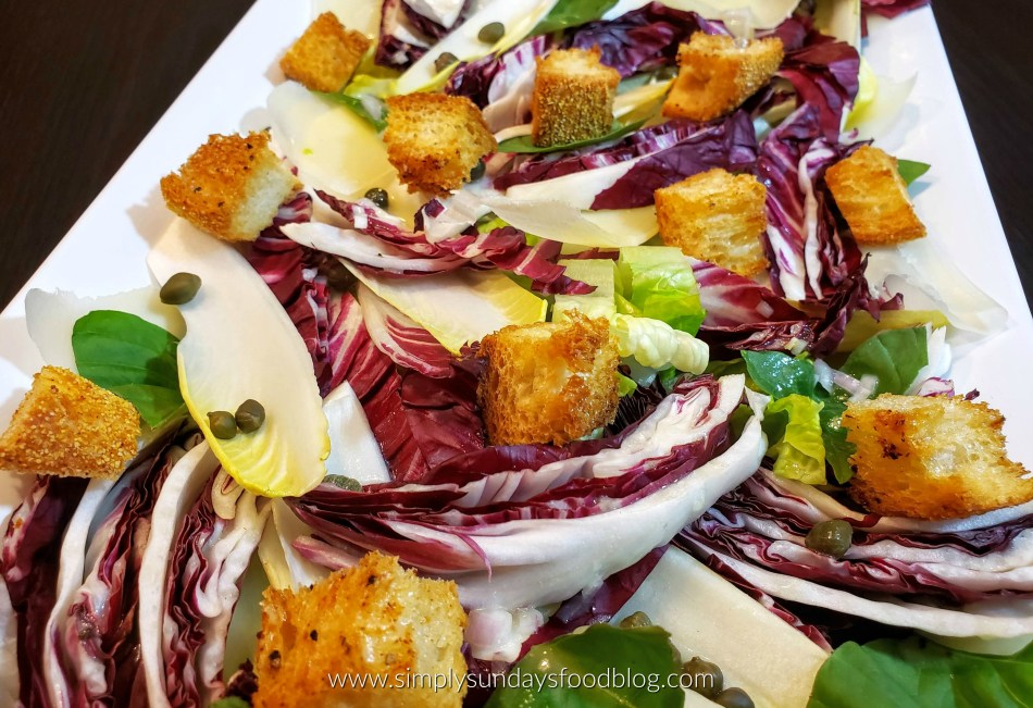 A platter of mild romaine lettuce, bold radicchio and crisp endive with crunchy homemade croutons, creamy parmesan drizzled with dijon vinaigrette