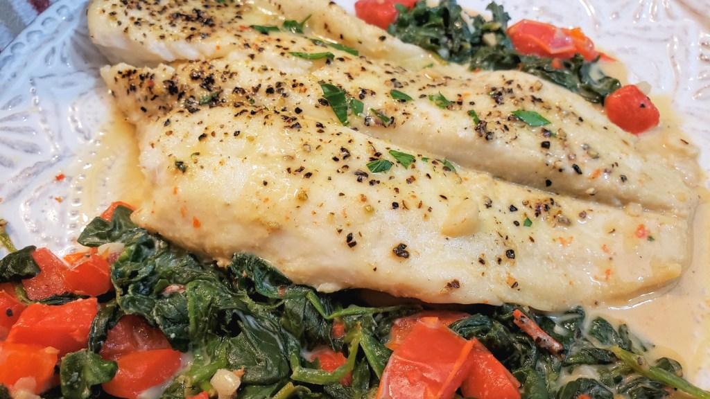 A fillet of flounder seasoned with salt, pepper and fresh parsley on a bed of spinach and red bell peppers with cream sauce