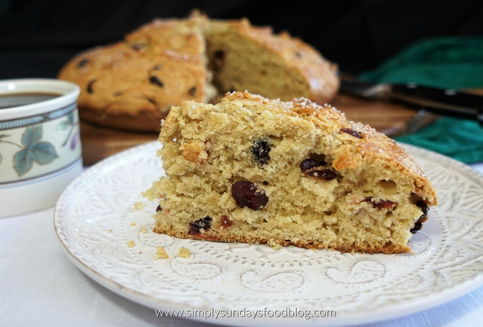 A slice of Irish Soda Bread on a white plate with a black cup of coffee. The whole cake and knife are in the background