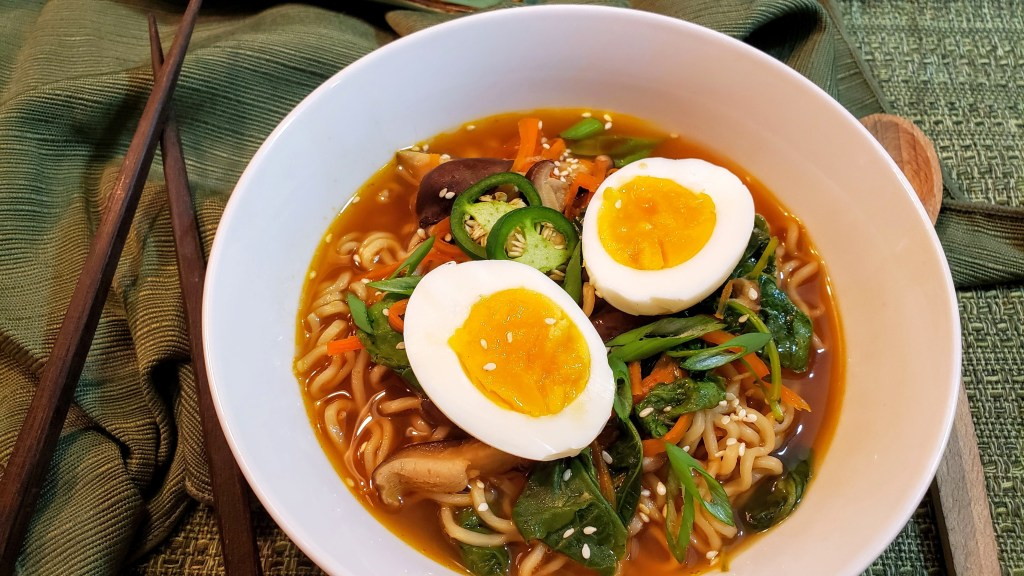 A large bowl of ramen soup garnished with soft boiled eggs, fresh jalapenos, scallions and sesame seeds