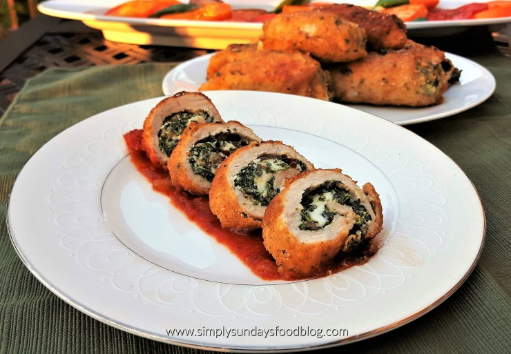 Four slices of rolled pork that was stuffed with spinach, mushrooms, ricotta and mozzarella cheese and coated in seasoned bread crumbs fried until a crisp golden brown served on a plate over a smear of tomato sauce on a white plate