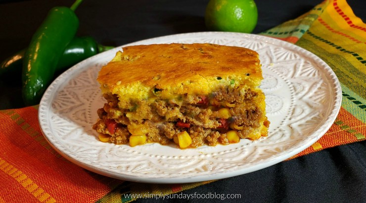 A square helping of chili cooked with ground turkey, peppers, onions, and cheese baked with a chive cornbread topping served on a white plate with some green jalapenos and a lime