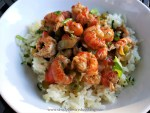 A stew of tender reddish pink crawfish in a colorful sauce of stock, red and green bell peppers over white rice sprinkled with fresh green chopped parsley and scallions