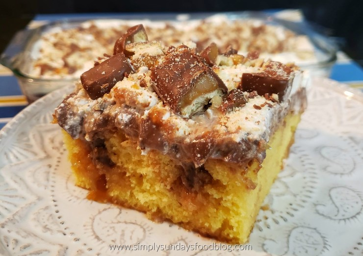 A close up photo of twix poke cake on a white plate
