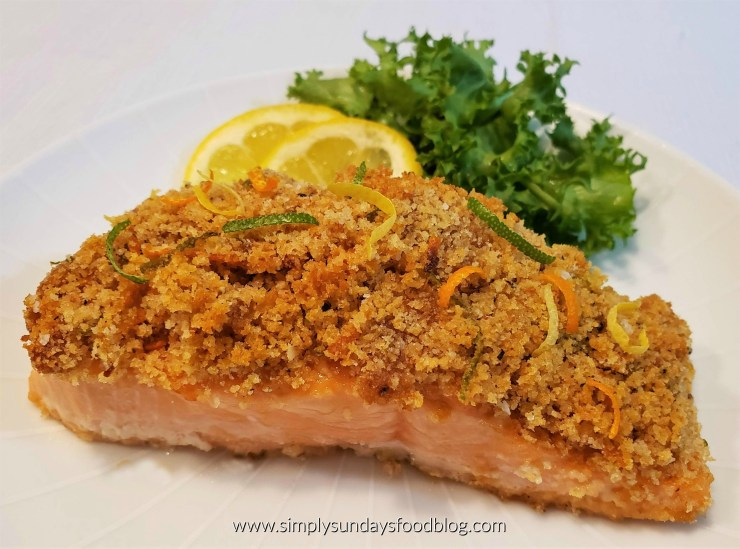 Pink salmon crusted with golden brown breadcrumbs that were mixed with orange, lemon and lime zest served on a white plate garnished with lemon wedges and fresh green chickory