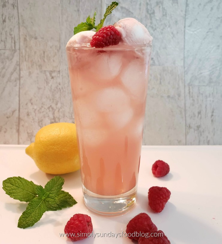 A tall glass filled with ice and the Malibu Rum Cooler. Garnished with fresh raspberries and mint with a whole lemon in the background