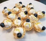 Lemon tartlets garnished with a fresh blueberry and lemon zest on a white marble board