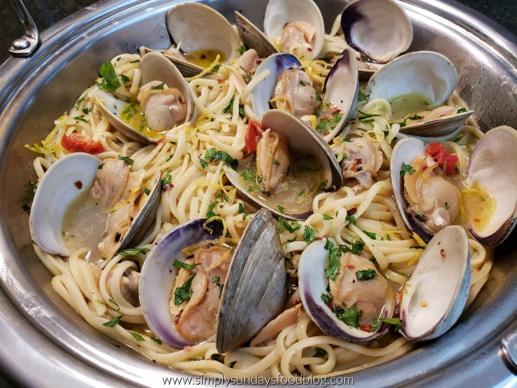 Linguine in a rich wine and garlic based sauce with whole and shucked clams nestled in the pan sprinkles with fresh green chopped parsley, yellow lemon zest and red strips of sundried tomatoes in a silver pan
