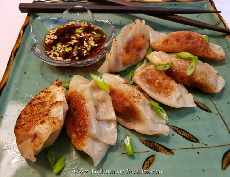Browned and crispy Asian pork dumplings on a green plate with fresh green scallions sprinkled around and a soy sesame dipping sauce to the side with a set of crossed chop sticks