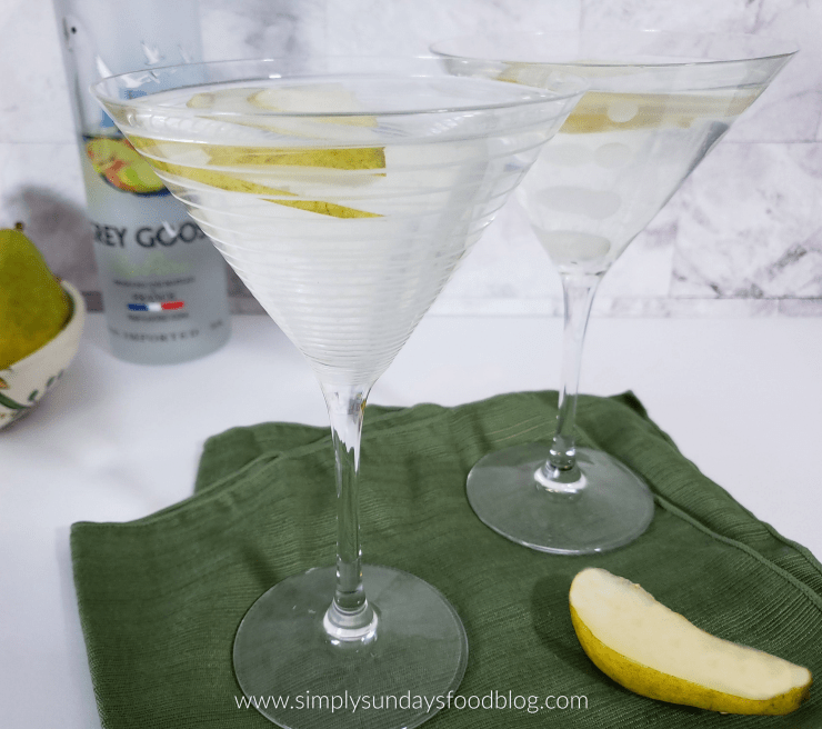 2 pear martinis on a green cloth with thin slices of pear floating and a bottle of Grey Goose vodka background