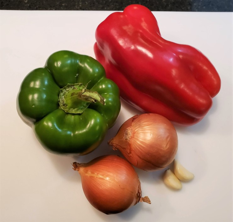 One red bell pepper, one green bell pepper, two onions and two garlic cloves on a white plastic cutting board