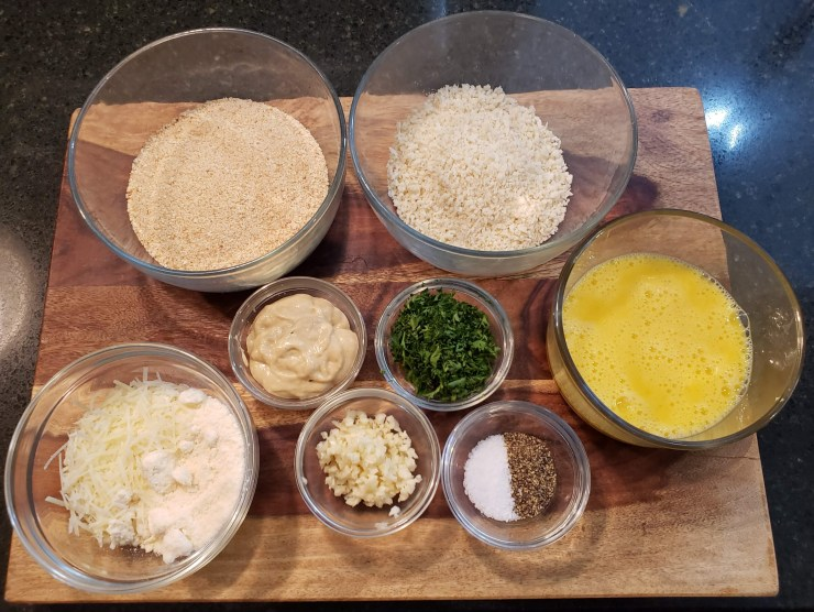 Eight clear bowls on a cutting board containing bread crumb, panko, whisked eggs, mustard, chopped parsley, chopped garlic, mozzarella and parmesan cheese and salt and pepper