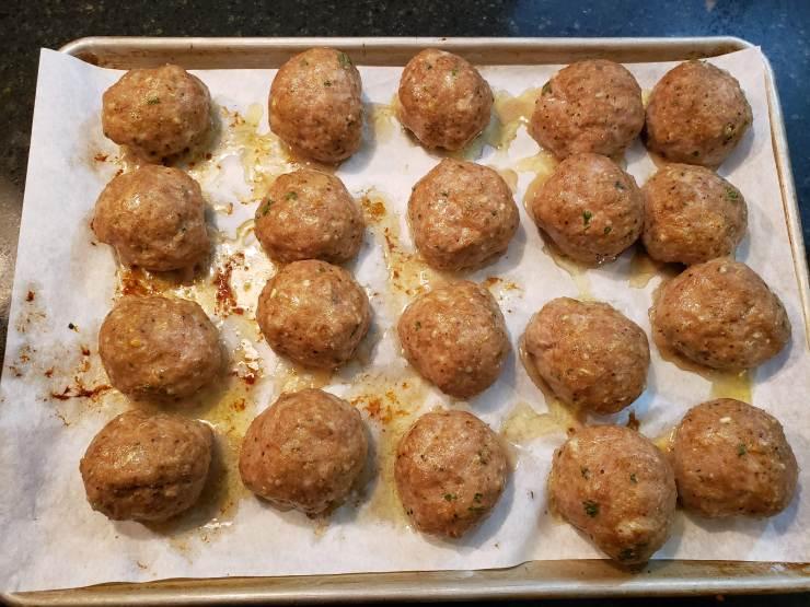 A sheet pan full of browned meatballs