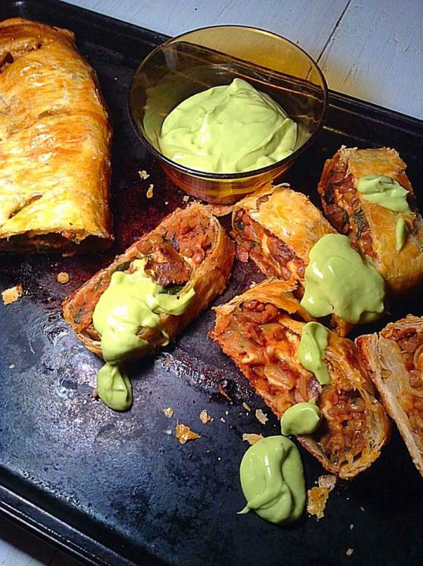 Lentil puff pastry roll with avocado sauce