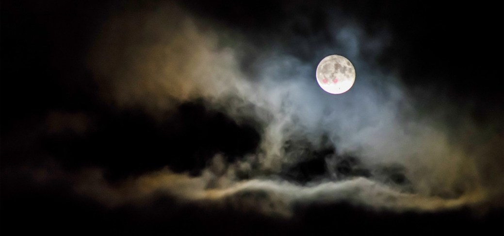 Ein Vollmond, der hinter Wolken verschwindet.