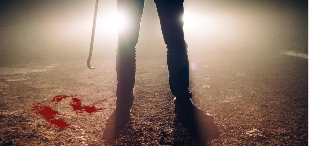 Im starken Gegenlicht sieht man die Beine eines Mannes und eine blutige Brechstange. Die Zahl Nummer 12 ist in Blut auf den Boden getropft.