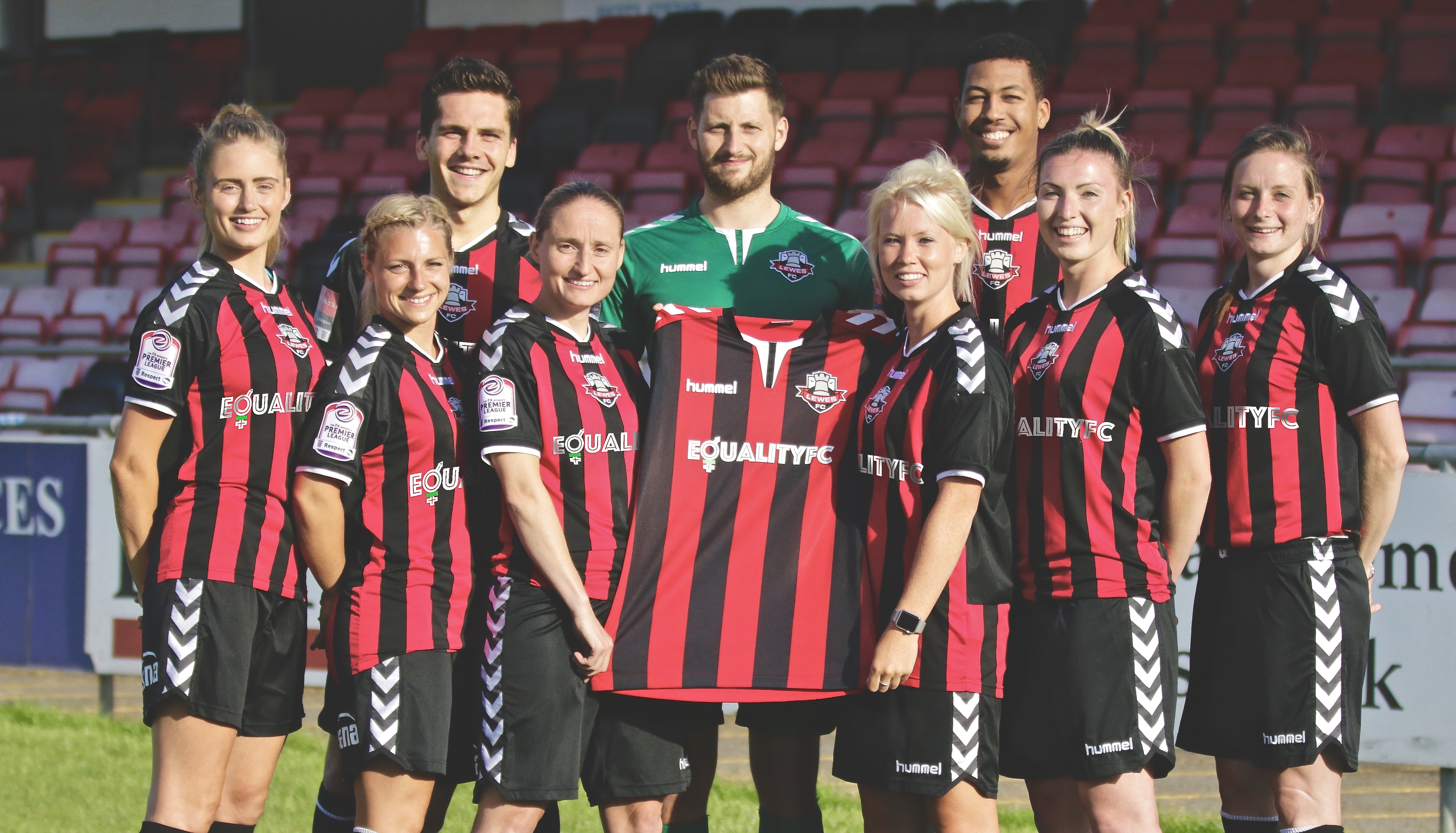 Lewes Football Club's men's and women's side pose with their home shirt.