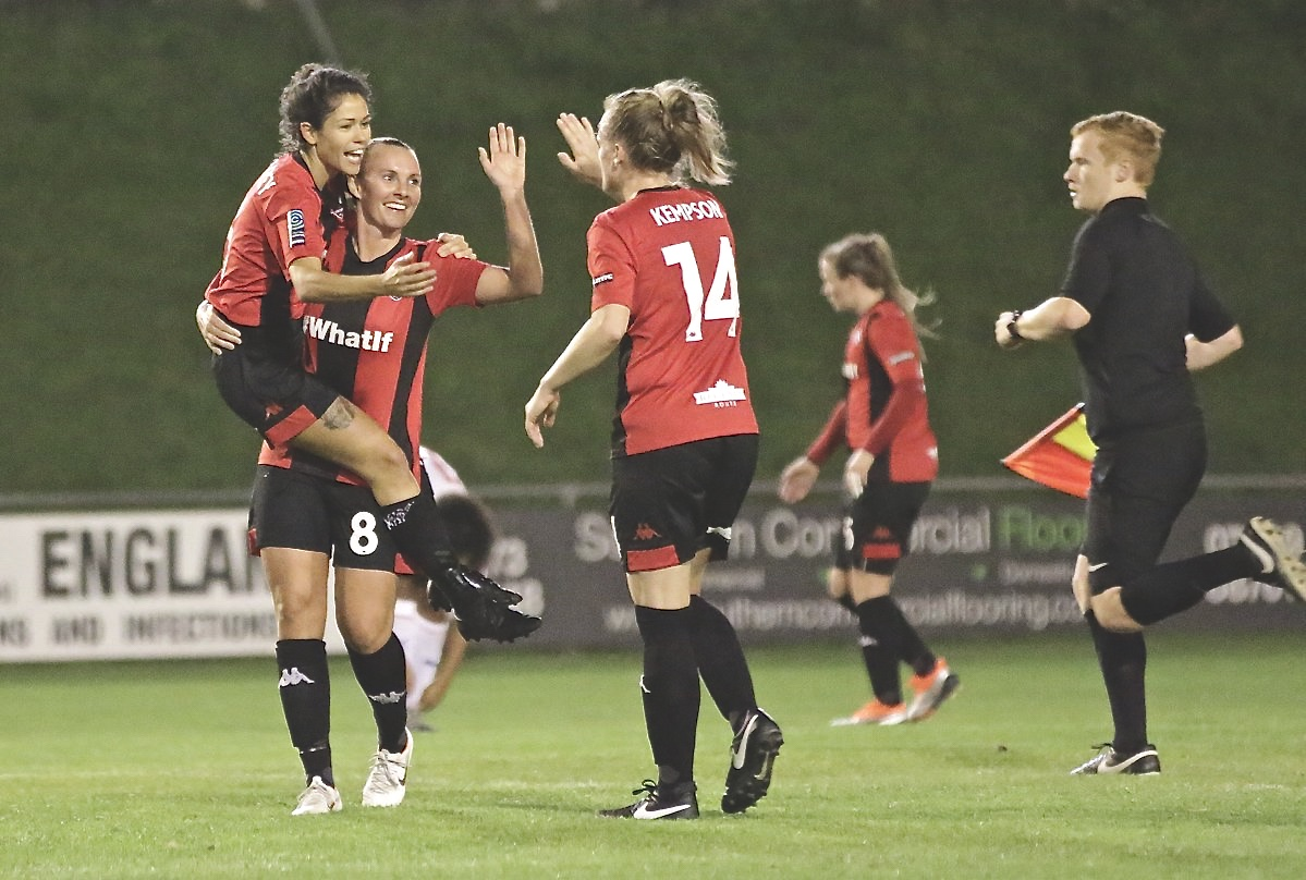 Lewes women's side celebrate a goal being scored.