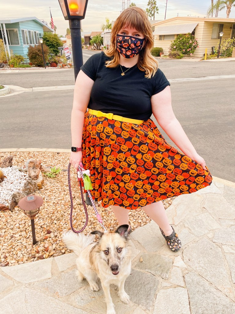 Curvy girl with blonde hair poses in skirt with pumpkins on it (which she made with her newfound sewing skills), holding it out to the side. Dog sits below, looking into camera.
