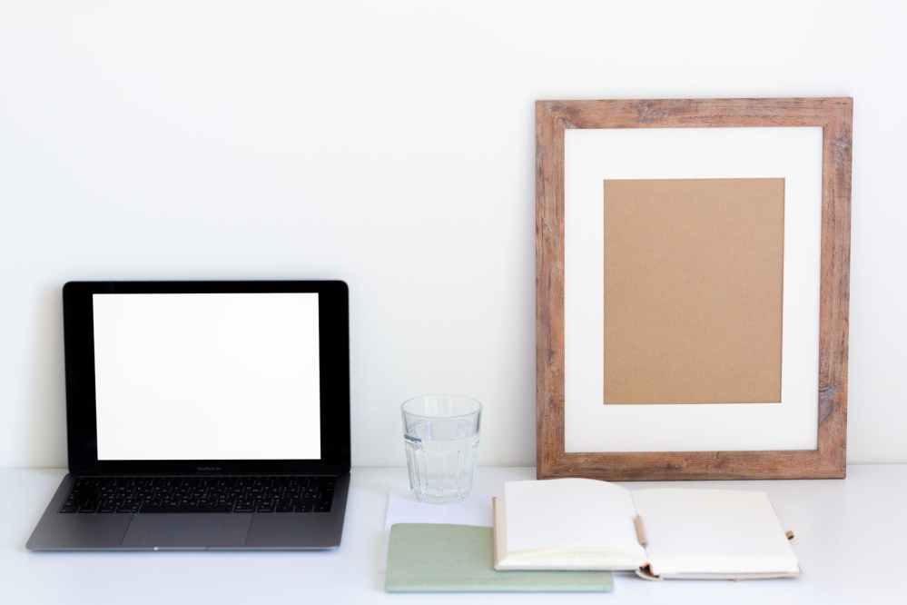 composition of netbook and frame near white organizer and glass of water on table