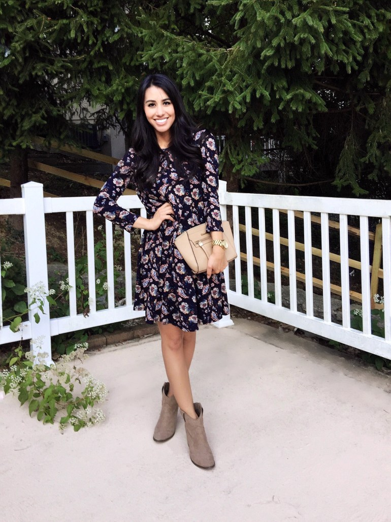 navy floral dress and wardrobe essential ankle boots against white fence