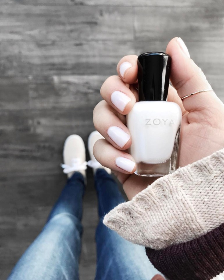 "manicure in neutral off-white shade, Zoya's ""Adel,"" blue jeans, canvas sneakers, beige sweater, burgundy bomber sleeve"