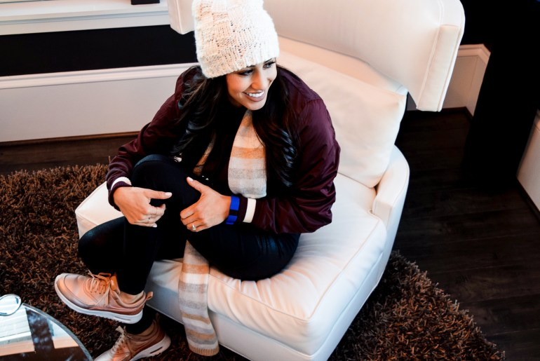 woman wearing white pom beanie, burgundy bomber, black leggings, white scarf, and rose gold nikes air max theas