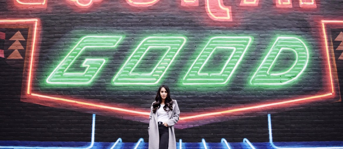 woman wearing gray duster coat, black fringe jeans, sparkle ankle boots in front of city mural
