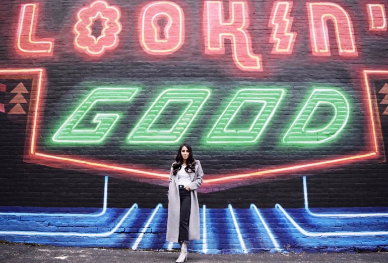 brunette woman wearing gray duster coat, black fringe jeans, sparkle ankle boots, and navy Tommy Hilfiger bag in front of a city mural