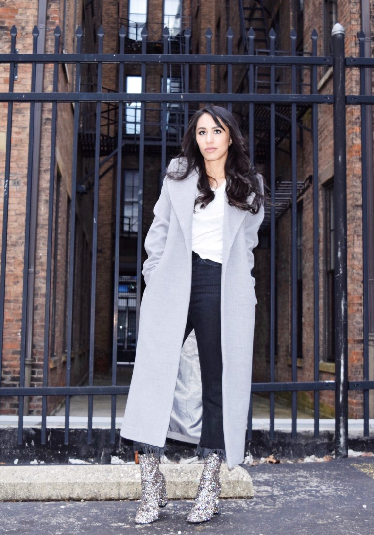 woman wearing gray duster coat, black fringe jeans, and sparkle ankle boots in front of black fence