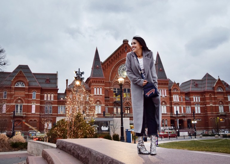 brunette woman wearing gray duster coat, black fringe jeans, sparkle ankle boots, and navy Tommy Hilfiger bag in front of Cincinnati's Music Hall