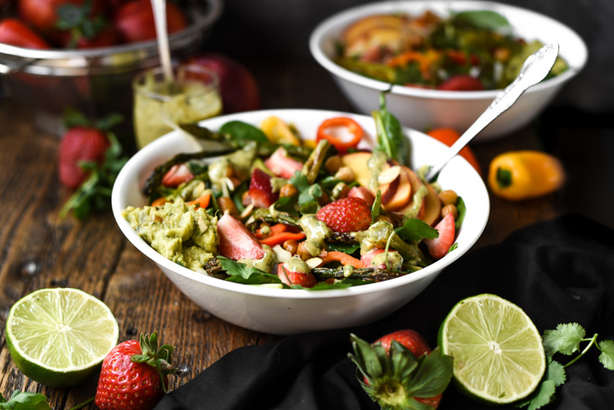 Photo of a coclorful salad for Spring. Salad recipe with strawberries, asparagus, peaches, dressing, spinach, and peppers. Springtime Vibes Salad+Cilantro Almond Butter Dressing (Vegan+GF)