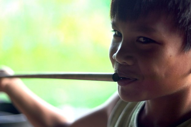 A young boy tries out the popoet, a unique bamboo flute. Copyright: Palmer Keen
