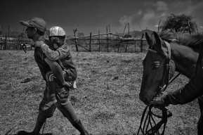 Indonesia, Sumbawa Island, Moyo, Every jockey is accompanied onto the track by his Sandro where he, the numbered jersey he'll wear and the horse he will ride are blessed before each race. The boy is then handed off to the trainer who will carry the young jockey down the long straightaway to the starting gate. Once a game between neighbors to celebrate a good harvest, horse racing was transformed into a spectator sport by the Dutch in the 20th century to entertain officials and nobility. The unique features of Sumbawa racing are the notoriously small horses and fearless child jockeys, aged 5-10, who mount bareback, barefoot and with little protective gear. Maen Jaran (the Indonesian name of the game) takes place during important festivals and holidays throughout the year at racetracks across the island and remains a favorite pastime for Sumbawans. Rules have evolved, horses are now classified by age and height, yet kid jockeys continue to risk their lives for 3,50 to 7 euros per mount often racing many times in one day, and every day during the racing week, pushed by parents and relatives given the potential earnings that far outweigh the poor returns on crops often plagued by drought.