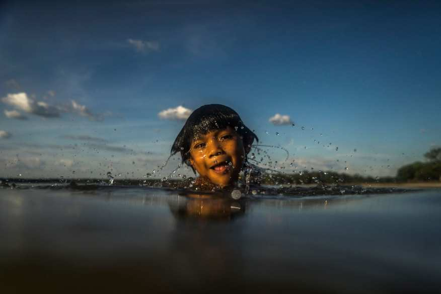 """2ND PLACE ARTISTIC MERIT- Ricardo Teles. In Xingu, midwest Brazil, the largest indigenous reserve in the world, the Kamayurás begin to walk towards Ypawu lake for their first bathing before sunrise. Several bathing sessions are going to be repeated daily until sunset. These waters are a link to their ancestors and keeping them pure is a sacred ritual. The lake is their most important source of food, and also the essence of their culture. The Kamayura´s creation myth tells about a magic bird which, in a dispute with a tribesman, threw up the water that formed the lake and also buried the residents. Since then, it has becomean enchanted place, and its water and plants a source of strenght for the Kamayurás. Once a year, the tribe holds the Kuarup, a festivalin honor to the dead. All neighboring tribes are welcomed to their territory on this occasion. The """"great spirits"""" are invoked to make sure there will be enough food for all the guests during the big fishing expeditions to Iananpau lake, which has remained untouched since the previous year´s celebrations and is bursting with life."""