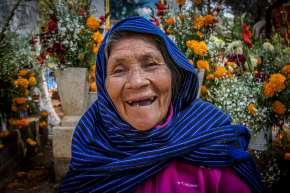 """Doña Josefina, 83, a descendant of the Perupecha, smiles as she sits in the tomb of her husband in Tzintzuntzan, Michoacan. The Perupecha begin their celebration of Dia de Los Muertos on November 1 and continue through the night of November 2. Once a month long celebration, it was shortened to coincide with the Spanish Catholic """"All Saints Day"""" and """"All Souls Day."""""""