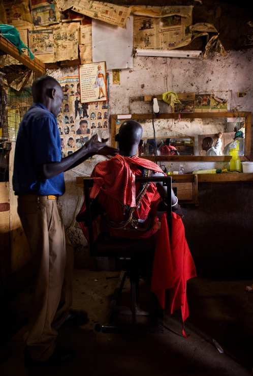 A tribesman discusses how his hair should be cut while sitting on a makeshift barber's chair. Even though the traditions and practices of the Masai tribes still intact, modern Western concepts are rapidly transforming the once simple nature devoted tribe.