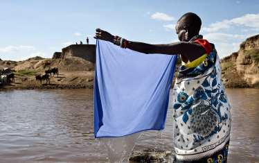 A 40 minutes walk from her village, a woman washes her clothes at the Masai river. On the other side of the river, men bring their cows to drink water.
