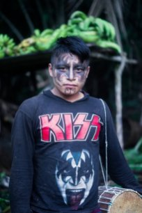 Lino Gualinga poses for a portrait during the first day of celebration of the Uyantza Raymi festival. During important festivities the Sarayaku people paint their faces with wituk, a dark pigment from a rainforest fruit. Usually they paint traditional motives that are inspired in jungle animals or deities. In this case he painted his face inspired in the Kiss rock band.