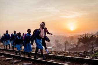 In the morning, children walk along the railway line in Kibera going to school. Education is still a big challenge in the slum, however most children achieve a secondary level education due to the support of numerous charities and non-governmental organizations based in Kibera. January 10, 2017. © Brian Otieno