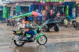 A motorcyclist navigates through heavy rains carrying school children back home. May 10, 2016. © Brian Otieno