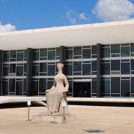 Sede do Supremo Tribunal Federal, edifício suspenso próximo ao chão com colunas modernas brancas e caixa de vidro escuro, com estátua da justiça sentada à frente.