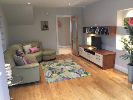 TV living area with green leather corner sofa, glass blocks