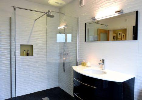 Monochrome bathroom design with recessed shelf/rainshower