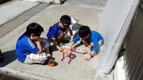 Shin Jen's workshop with 3 children working on the solar cooker outdoors