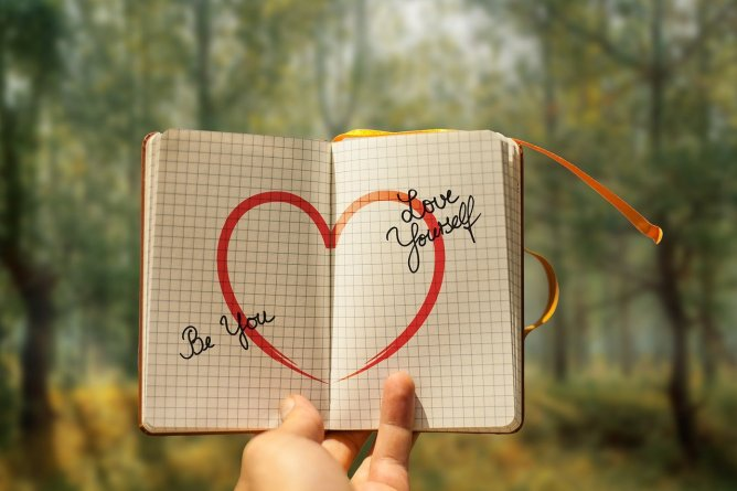 An open journal with a heart drawn on it, saying Be You, Love Yourself.