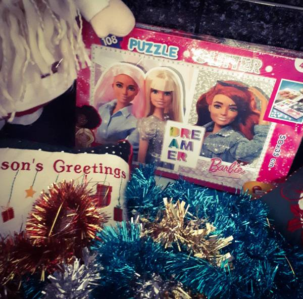 The Barbie Jigsaw puzzle box resting by some tinsel and christmas-themed cushions